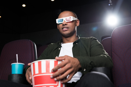 african american man in 3d glasses eating popcorn and watching film in cinema