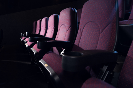 row of red seats in empty dark cinema