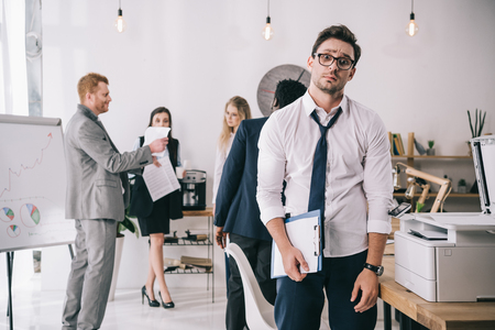 bewildered overworked businessman standing in office with blurred colleagues working on background Foto de archivo