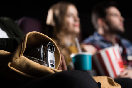 selective focus of people with video camera pirating in cinema
