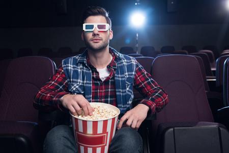 handsome man in 3d glasses with popcorn watching movie in cinema Banco de Imagens