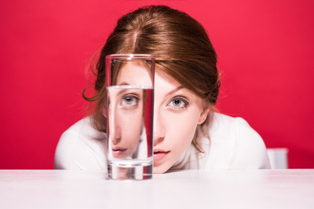 upset young woman looking through glass of water isolated on red