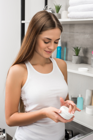 Beautiful woman taking cream in a bathroom Standard-Bild