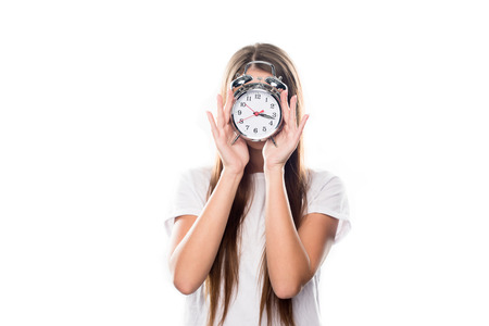 Girl covering face with alarm clock isolated on white