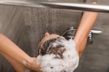 Vue de dessus de fille laver les cheveux avec du shampoing sous la douche