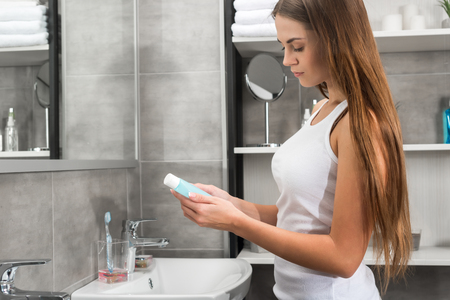 woman reading lotion description in the bathroom Stockfoto