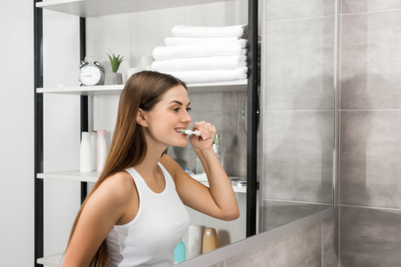 Woman in white singlet brushing teeth in the bathroom