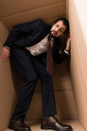 businessman in suit with claustrophobia inside a box Stock Photo