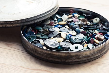 lot of buttons in circle box over wooden background Banco de Imagens