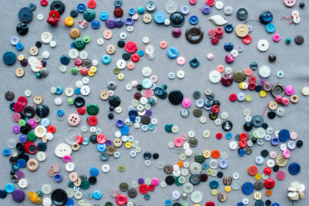 top view of scattered colorful buttons on grey cloth background 스톡 콘텐츠