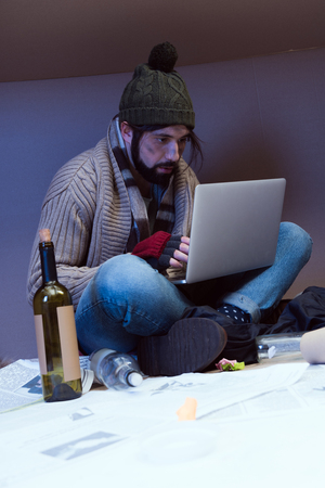 homeless muddy man using laptop while sitting in big cardboard box Stock Photo