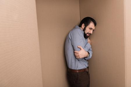 depressed lonely man huging himself in cardboard box