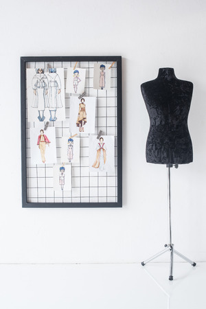 frame with fashion sketches hanged on white checkered background and black mannequin