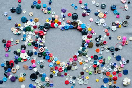 top view of colorful buttons heart shaped frame on grey cloth background Stockfoto