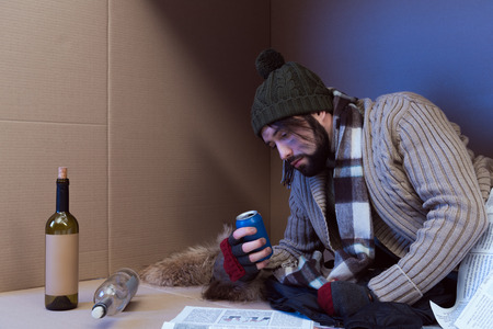 homeless man with alcohol drinks in cardboard box