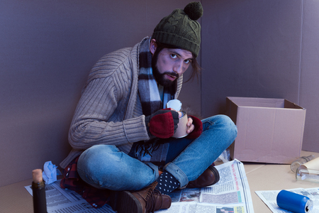 homeless man eating canned food in cardboard box Stock Photo