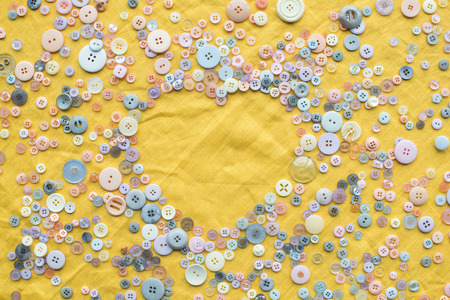 top view of colorful buttons heart shaped frame on yellow cloth background with copy space