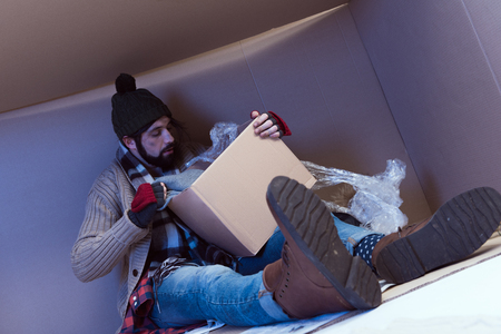 homeless man with box sitting in big cardboard box Stock fotó