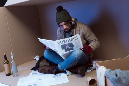homeless man reading business newspaper in cardboard box