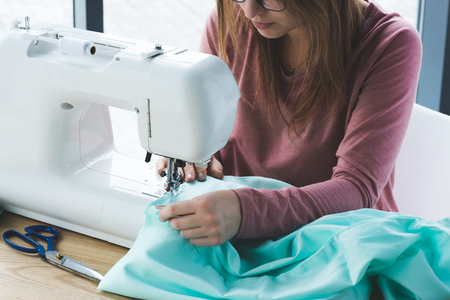 cropped image of young seamstress using sewing machine at workplace Stock Photo