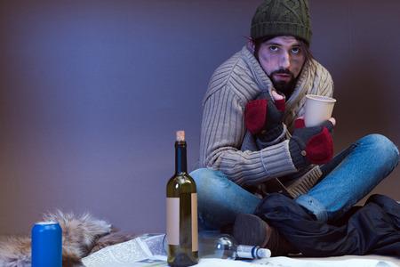 frozen homeless poor man asking for alms in cardboard box Foto de archivo - 104663604