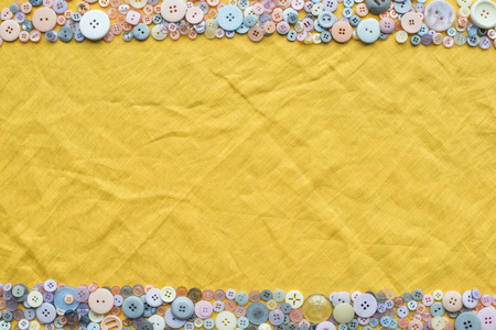 top view of colorful buttons frame on yellow cloth background with copy space Imagens
