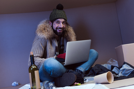 cheerful homeless man using laptop while sitting in big cardboard box Stock Photo