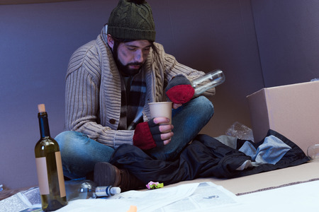 homeless alcoholic drunking in cardboard box
