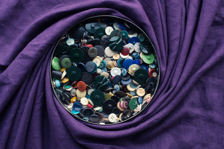 lot of buttons in circle box, covered by purple fabric