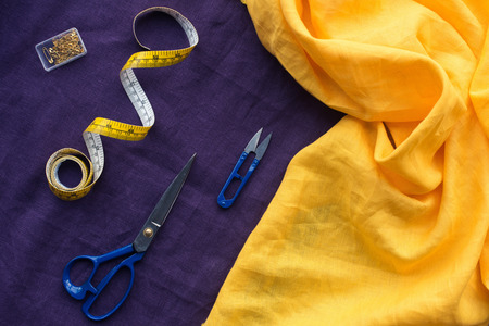 top view of scissors, measuring tape and box with pins over purple fabric Imagens