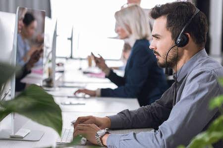 Mise au point sélective de l'opérateur du centre d'appels ciblé dans le casque travaillant au bureau Banque d'images