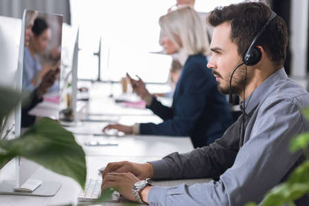 selective focus of focused call center operator in headset working in office Standard-Bild