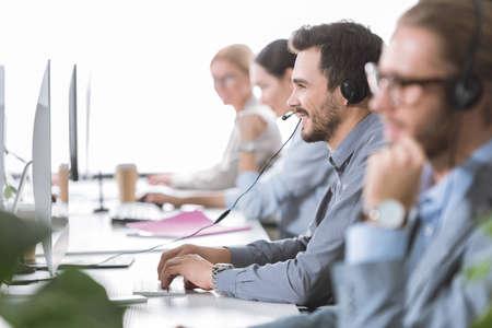 Mise au point sélective de l'opérateur de centre d'appels souriant dans le casque travaillant au bureau