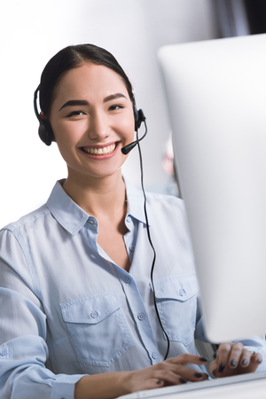 portrait of smiling asian call center operator in headset looking at camera