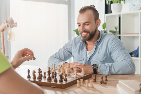 young man playing chess with opponent