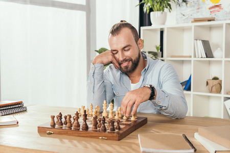 smiling thoughtful man playing chess with himself 写真素材