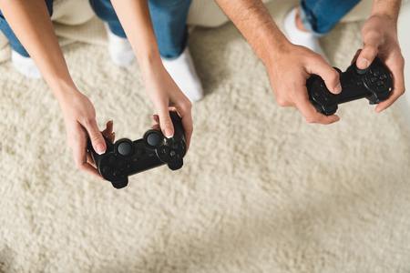 top view of couple playing computer games with gamepads