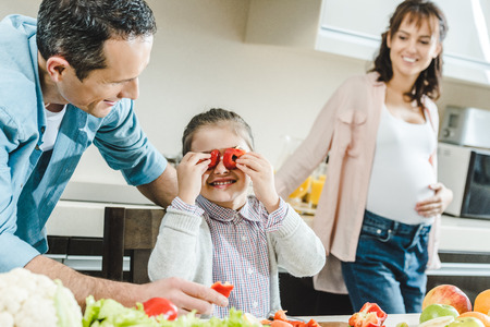 happy family, little kid applies pepper slices to eyes when father and pregnant mother watching on her at kitchen