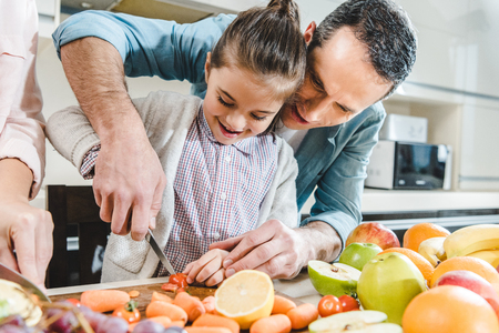 happy father with daughter slicing vegetables and fruits on chopping board at kitchen