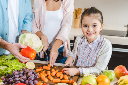 cropped image of family at kitchen, little kid with mother slicing vegetables and looking at camera