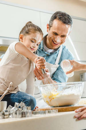 happy family, little kid with father mixing dough in bowl by hands at kitchen