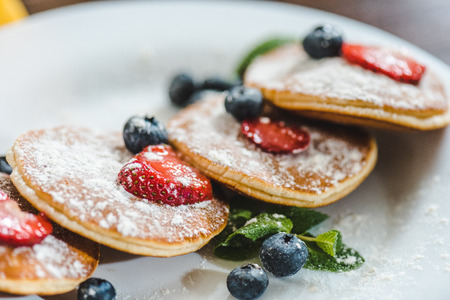 closeup pancakes with berries and mint on white plate Stok Fotoğraf