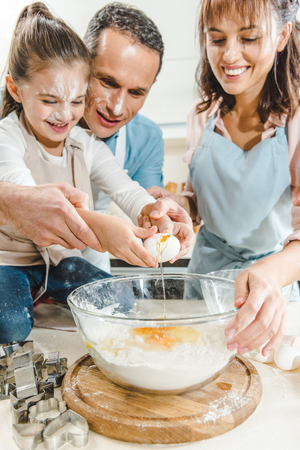 cropped image of happy family splitting egg in bowl at kitchen Stock Photo