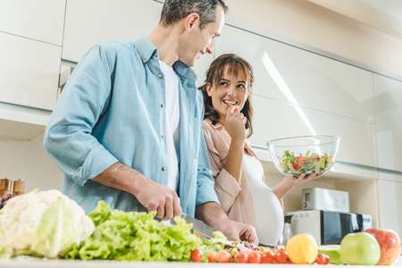 happy pregnant couple at kitchen making salad and looking at each other Imagens