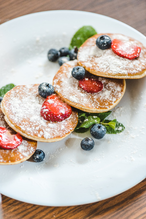 closeup of pancakes with berries and mint on white plate