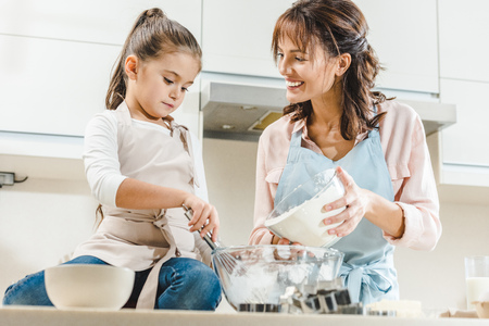happy mother with daughter making dough at kitchen 免版税图像