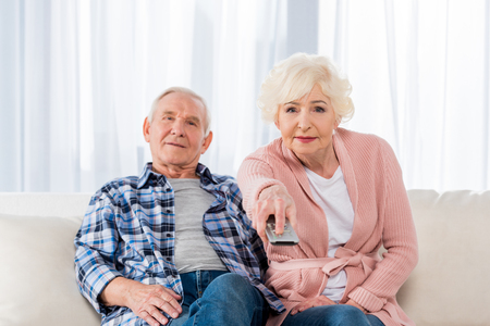 senior couple with remote control watching tv on couch 版權商用圖片