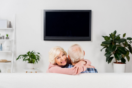 senior couple embracing on couch in front of tv Stok Fotoğraf