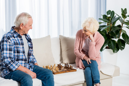 concentrated senior couple playing chess at home on couch
