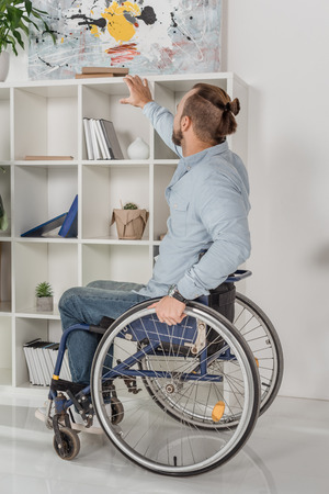 disabled man on wheelchair trying to reach for book on bookshelves Banco de Imagens